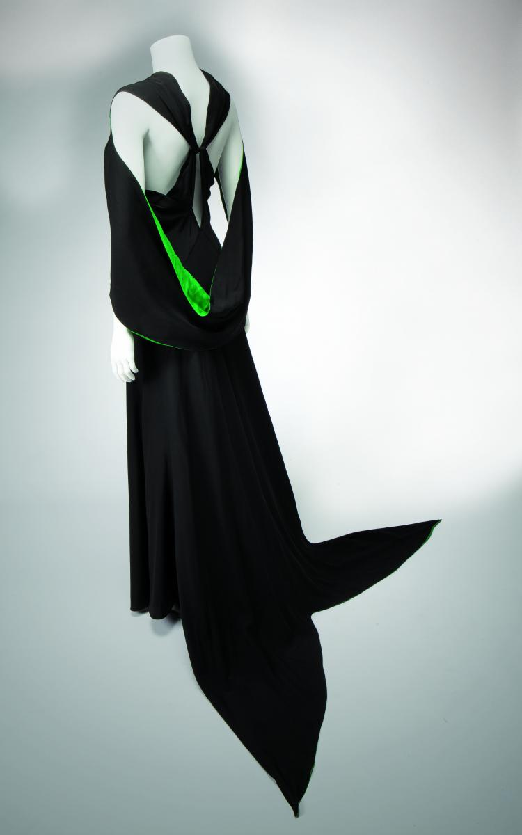 Image of black halter crepe evening dress with green accents on a white background.