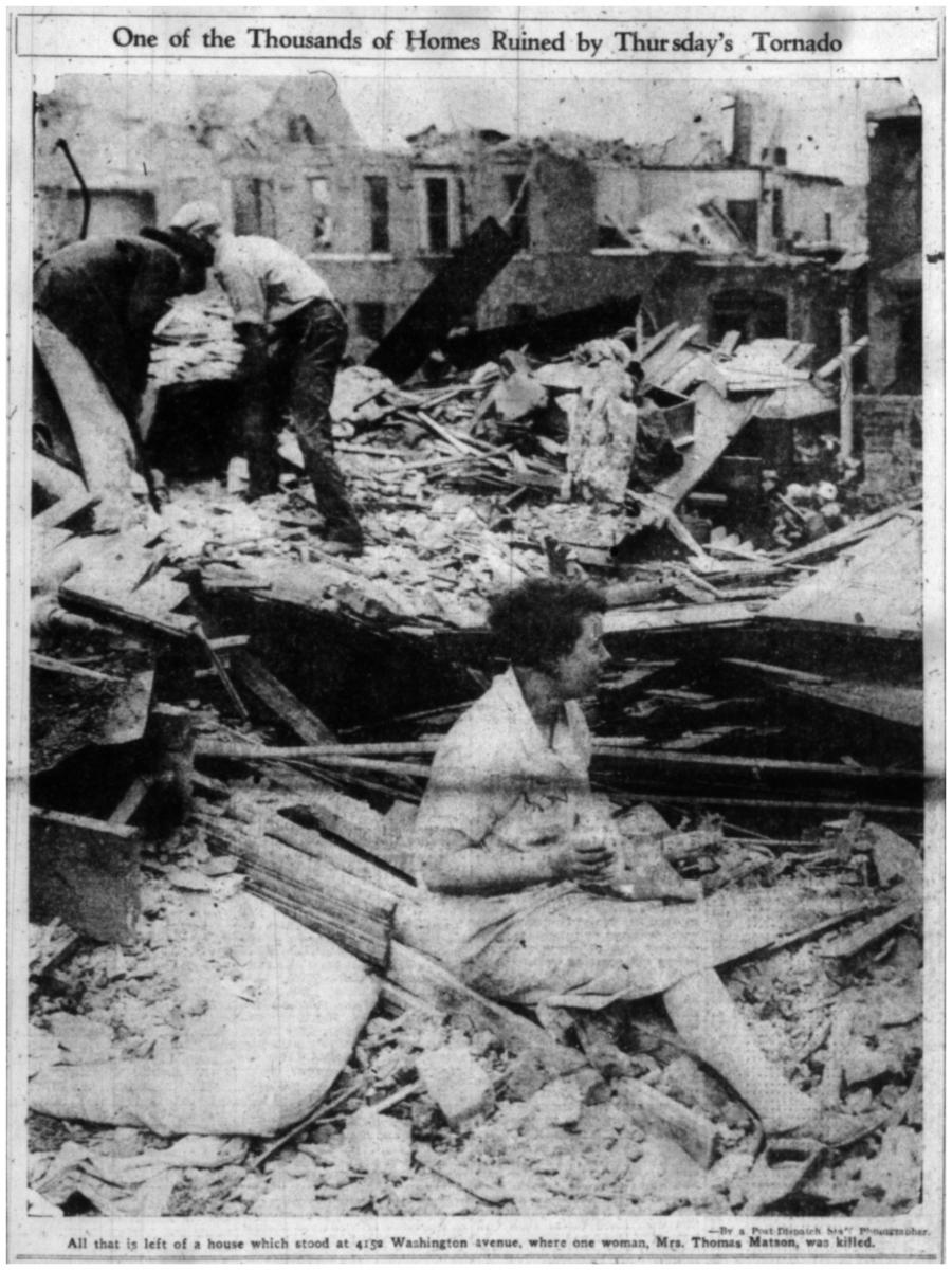 Black-and-white scan of newspaper photo showing woman sitting amidst the ruins of a house