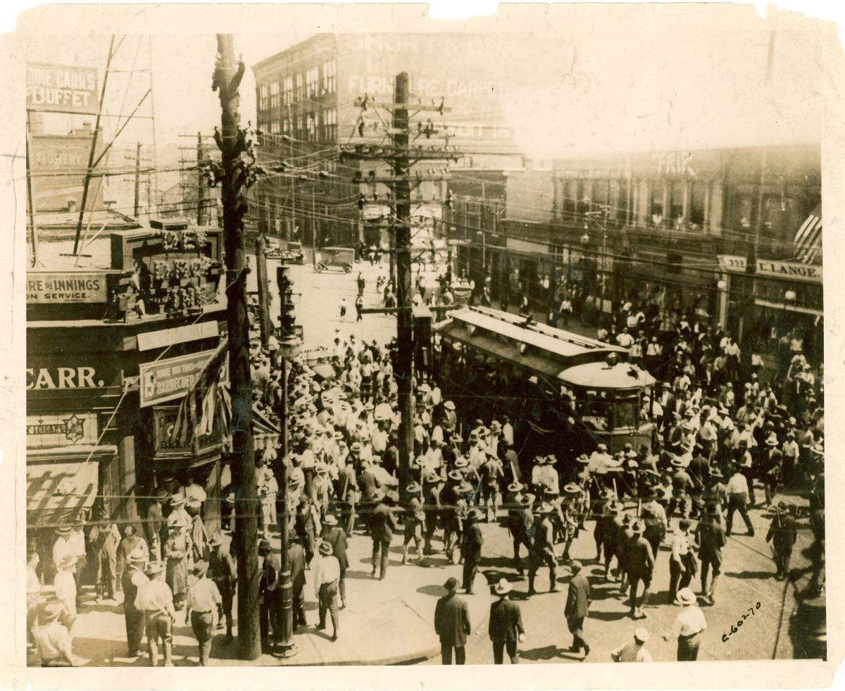 Sepia-toned photo of white mob surrounding streetcar during East St. Louis riot