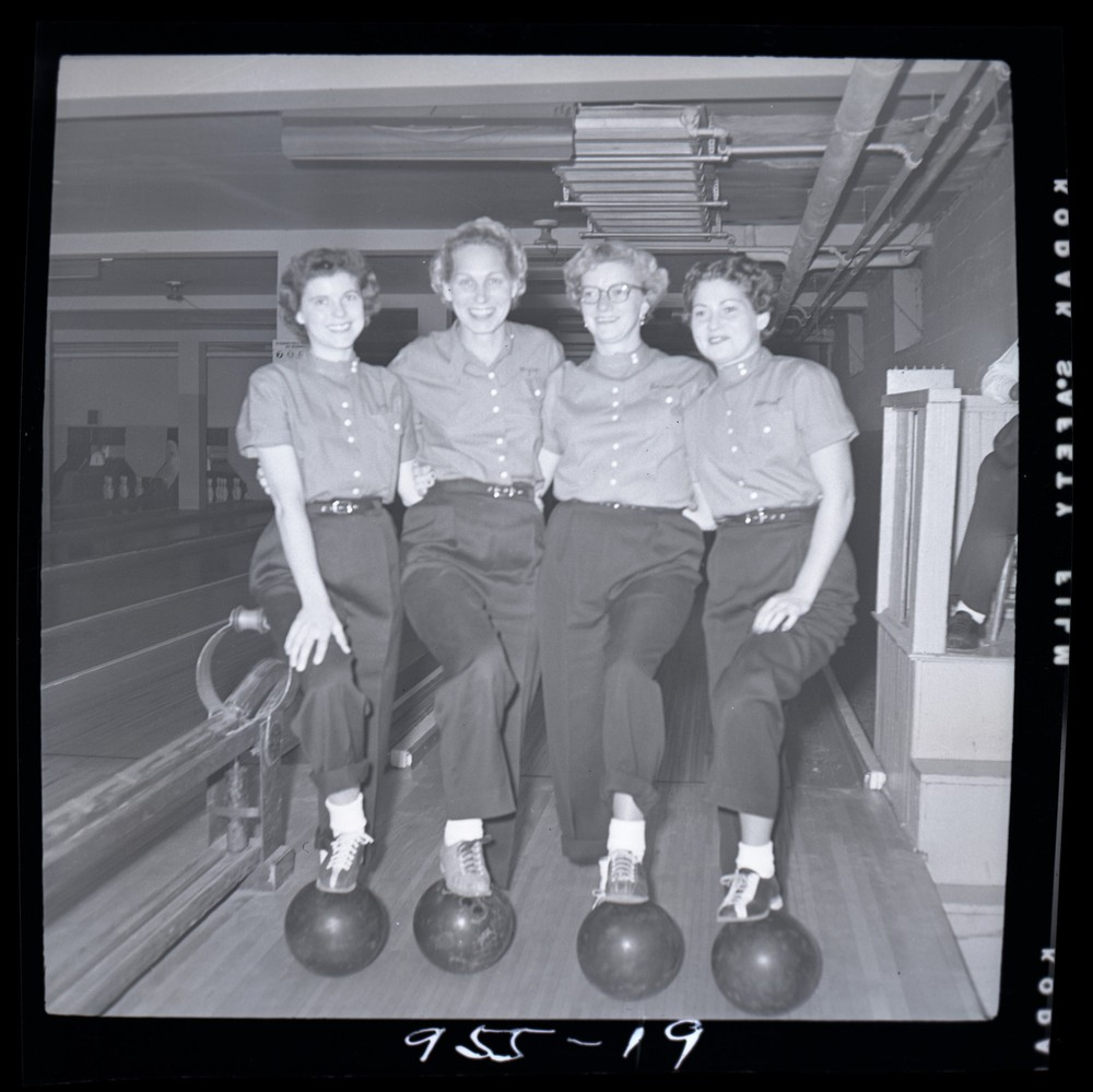 Black-and-white photo of four women at bowling alley