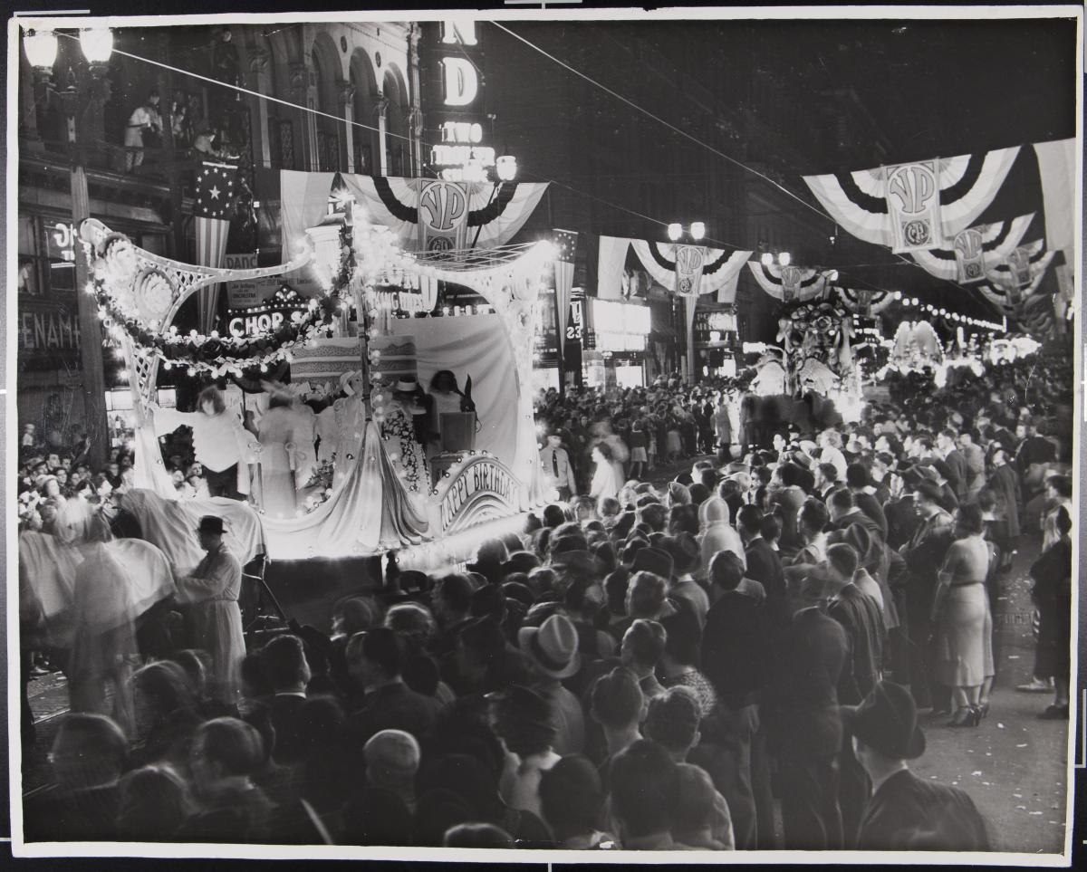 Black-and-white photo of crowd watching a passing float at the 1937 Veiled Prophet parade