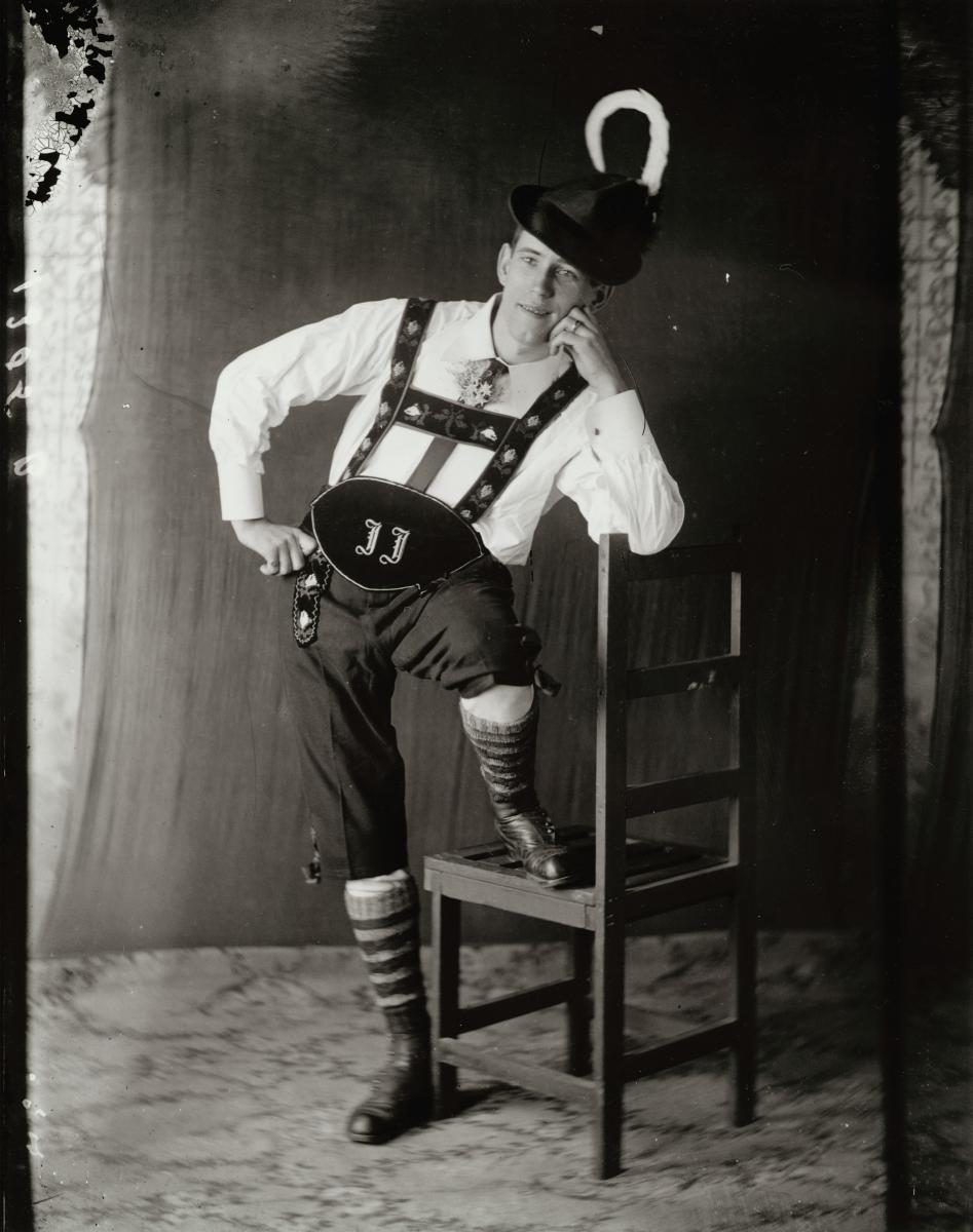 A vertical black-and-white portrait of a man in lederhosen and a Tyrolean hat.