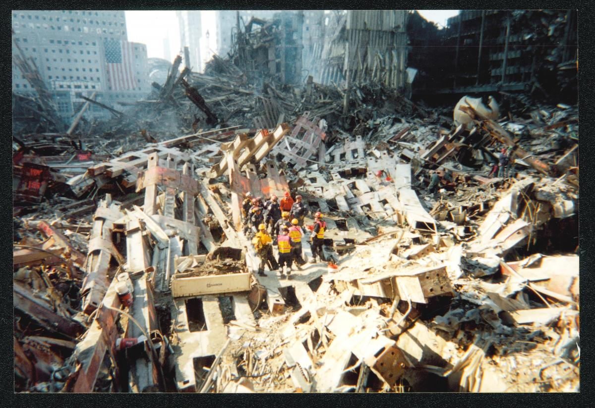 Color photo of rescue workers amidst wreckage of the World Trade Center