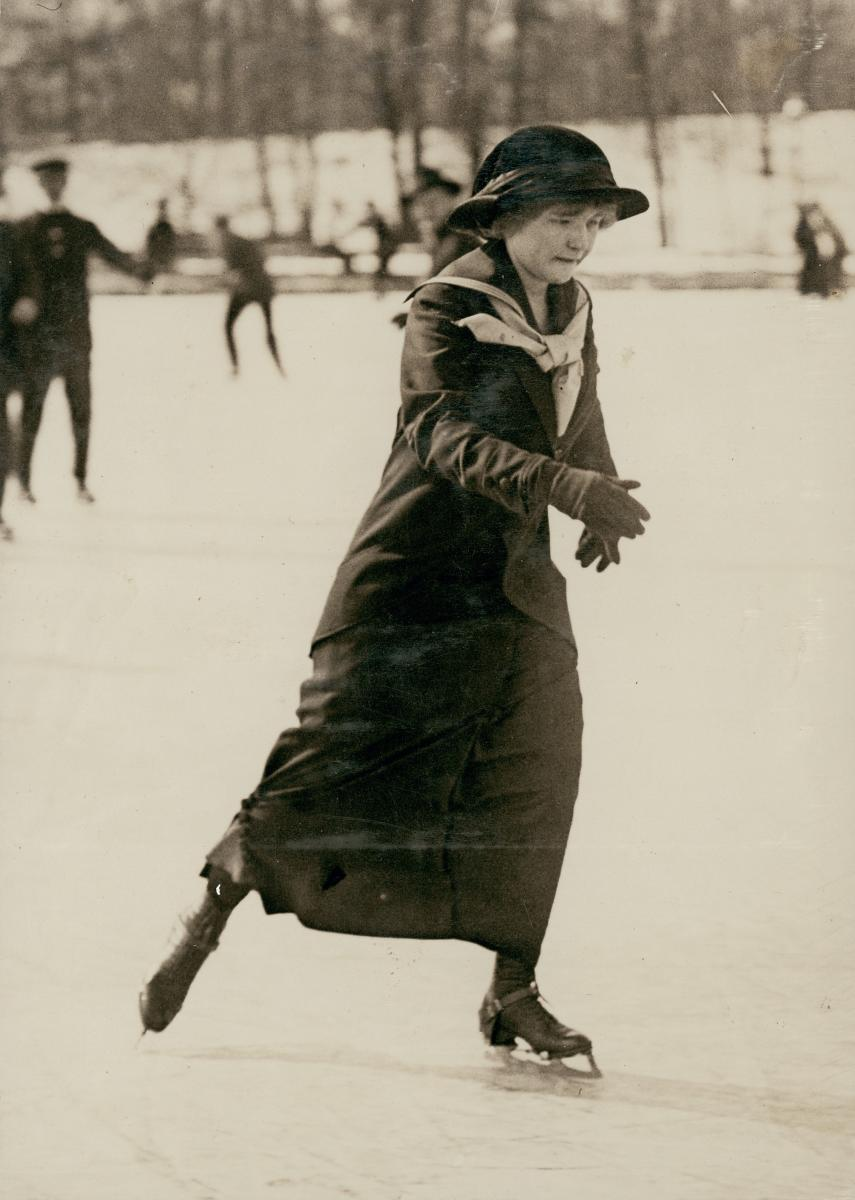 Vertical sepia photo of a woman in a hat ice-skating in the park.