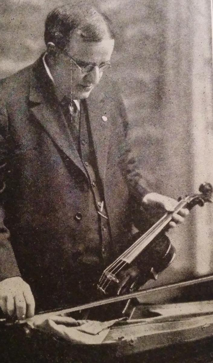 Dr. John Gaines, poet, physician, and composer, holding his fiddle