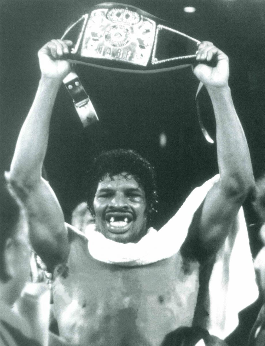 Black-and-white photo of Leon Spinks holding title belt