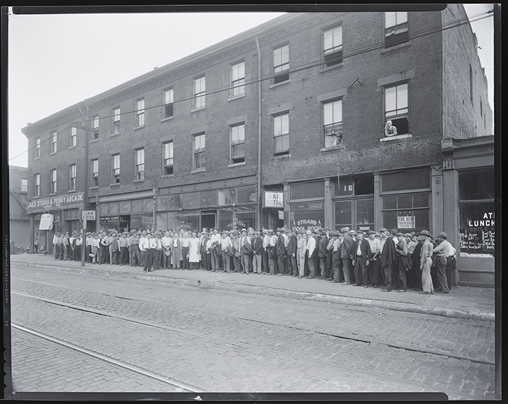 Black-and-white photo showing men lined up on Market Street, waiting for food and work