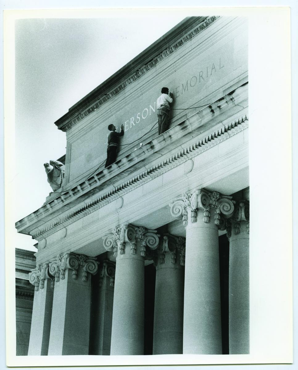 Photo of workers painting the sin on the Jefferson Memorial Building