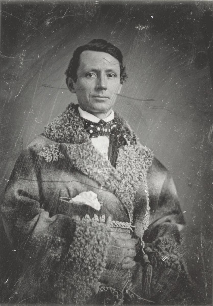 A black-and-white portrait of a man in a polka-dot cravat and a coat trimmed in lamb's wool.