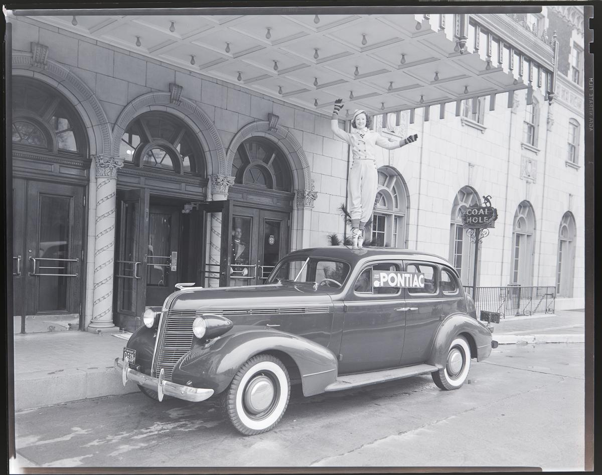 Blakc-and-white photo of dancer posed atop a car outside the Coronado Hotel