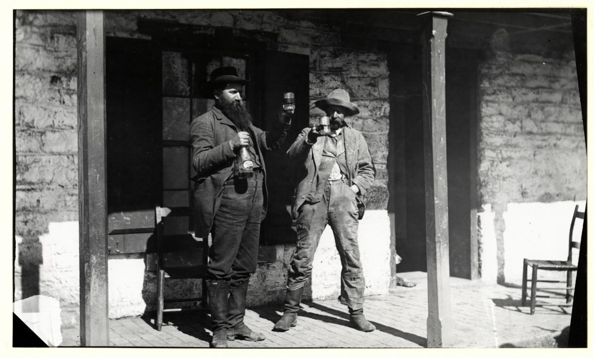 Black and white photo of two men standing on the wooden porch of a stone building hoisting mugs of beer.