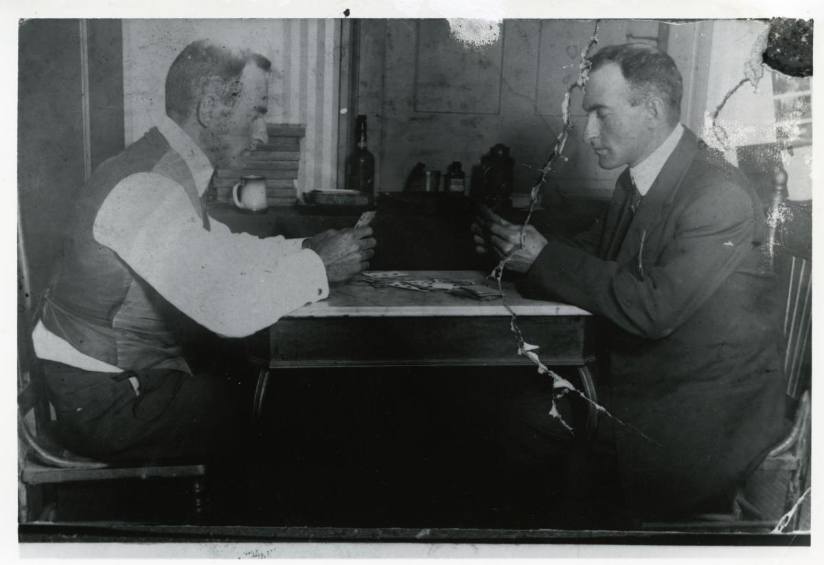 Black-and-white photo of Isaac Sievers playing cards with himself