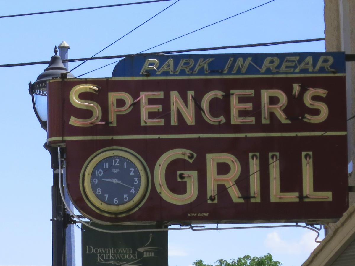 Color photo of the red Spencer's Grill sign and analog clock