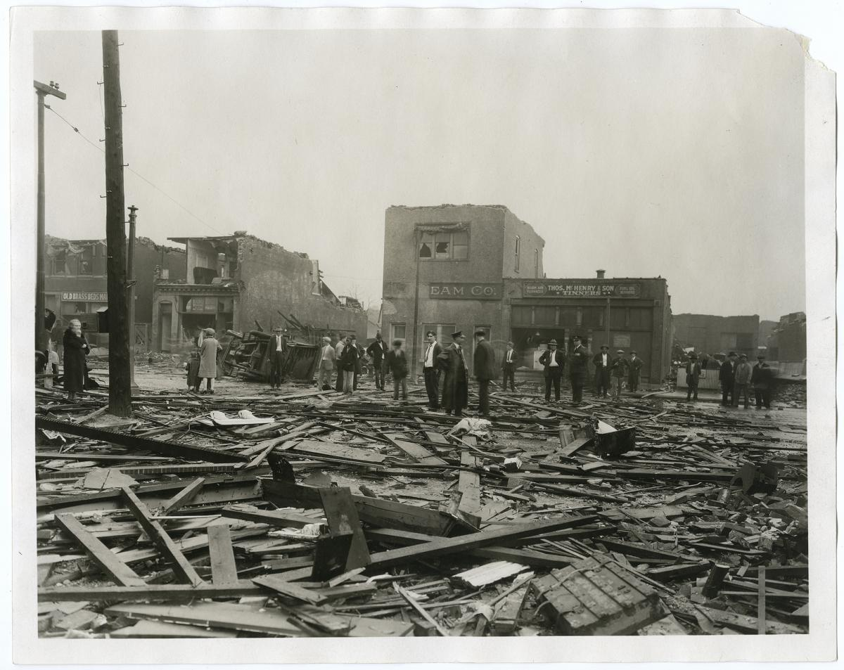 Sepia-toned photograph of spectators standing in rubble left behind by the 1927 tornado