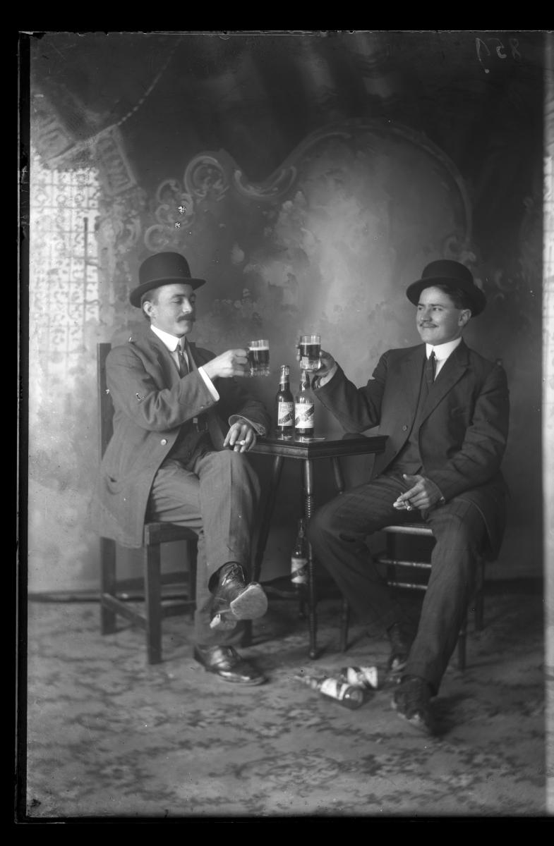 Vertical black-and-white portrait of two men drinking Louis Obert Gold beer.