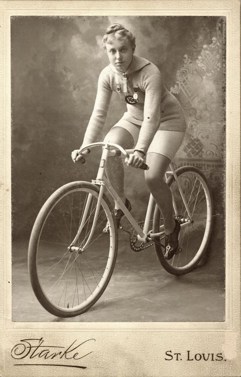 Black and white studio photograph of Mrs. Minnie. She's balanced on her bike facing the left of the camera. In front of a backdrop.