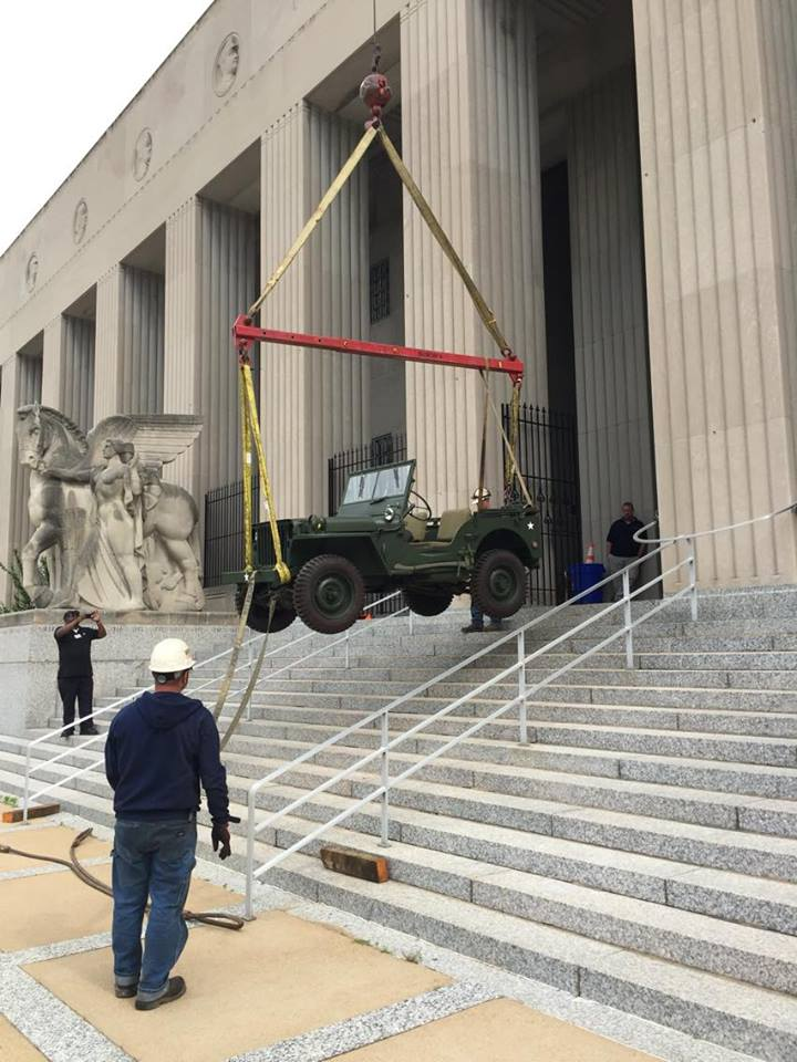 Jeep being moved via crane.