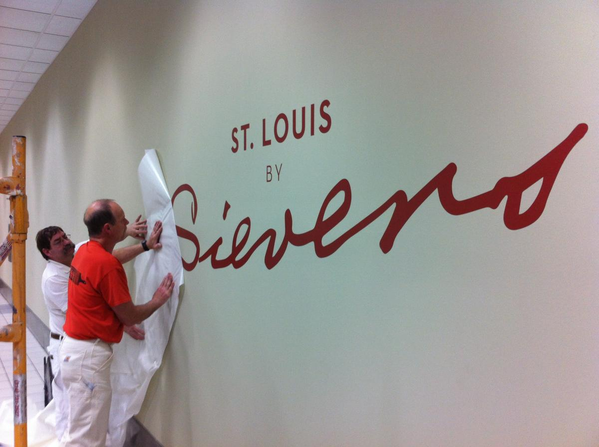 "Workers install the ""St. Louis by Sievers"" exhibit at Lambert Airport in April 2016."